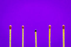 Burned match setting on purple background for ideas and inspirat Stock Photo