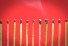 Burned match setting on red background for ideas and inspiration Royalty Free Stock Photography