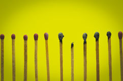 Burned match setting on yellow background for ideas and inspirat Stock Image