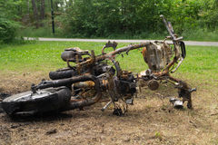 Burned motorcycle laying on the ground metal garbage background Stock Photos