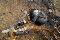 Burned motorcycle laying on the ground metal garbage background Royalty Free Stock Photography