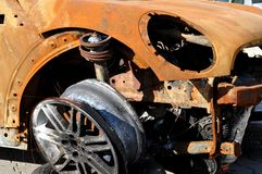 Burned out auto wreck. Buned out and rusted auto wreck with alloy wheel Stock Photography