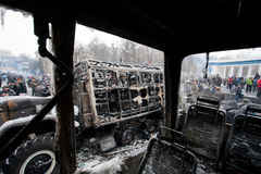 Burned out buses and military auto stand in the occupying street with crowd of protesters during riot Royalty Free Stock Image