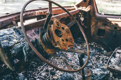 Burned out car, inside view, rusty steering wheel, stock photo