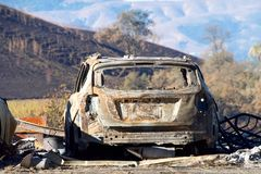 Burned out car in Northern California. Car burned in the North Bay firestorm, charred landscape in the background Royalty Free Stock Photos