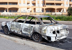 Burned out car in street Stock Photos