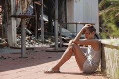 Burned out house. Sad woman sitting in front of burned out house stock photography