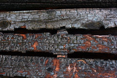 Burned-out wall of wooden planks in ashes Stock Photo