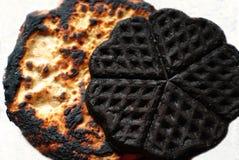 Burned pancake. Two burned pancake on white background Royalty Free Stock Images