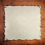 Burned paper. The burned paper on the wood background Royalty Free Stock Photos