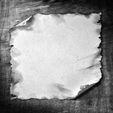 Burned paper. The burned paper on the wood background for designs stock images