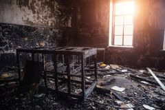 Burned room interior in apartment house. Burned furniture and charred walls in black soot Stock Photography
