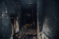 Burned room interior in apartment house. Burned furniture and charred walls in black soot Stock Photos