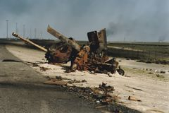 Burned shell of Iraqi tank on side of road, Kuwait. Burned bombed shell of  Iraqi tank on side of roadway in Kuwait following Operation Desert Storm during the Royalty Free Stock Image