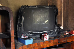 Burned television after a house fire. Ruins of a destroyed residence after a house fire Royalty Free Stock Photography