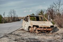 Burned to the ground car wreck on the side of the road stock photo