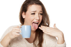 Burned tongue. Young woman with burned tongue from her hot tea Stock Images
