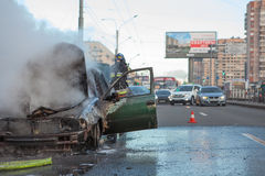 Burned vehicle with smoke on city street Stock Image