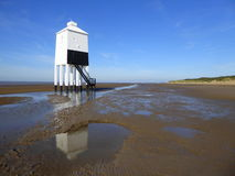 Wooden lighthouse on beach at low tide Stock Images
