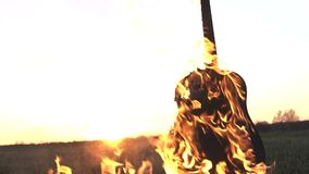 Burning acoustic guitar on fire close up. In the field at sunset stock video footage