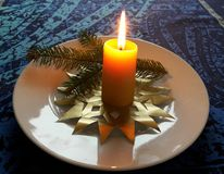 Burning advent candle on a table Stock Images