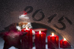 Burning advent candles on the frosted window with 2015 new year' Royalty Free Stock Images