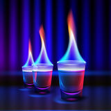 Burning alcohol shots. Vector burning cocktail shots with colored fire and blue, red backlight on blur dark illuminated background Vector Illustration