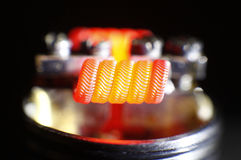 Burning alien coil build on vaping rebuildable dripping atomizer Stock Photography