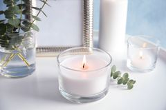 Burning aromatic candle and eucalyptus branch. On table royalty free stock photos