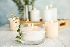 Burning aromatic candle and eucalyptus branch. On table stock photography