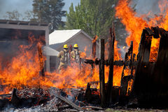 Burning barn and firefighters. Stock Photos