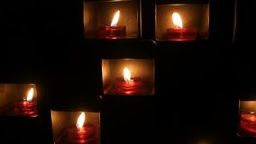 Burning beautiful red round prayer candles in a special niche in the darkness of a Catholic church. stock video