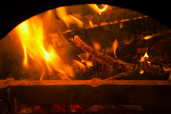 Burning billets and branches in fireplace. Royalty Free Stock Photography