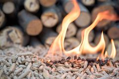 Burning biomass bellets. Renewable energy - wooden pellets in fire stock photo