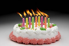 Burning Birthday candles. Colorful Flaming candles on a decorated cake Stock Photography