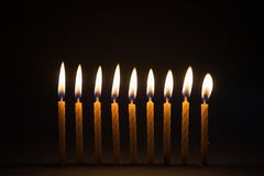 Burning birthday candles with black background. Burning row of birthday candles with dark black background royalty free stock photography
