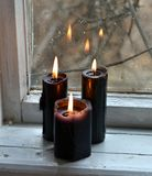 Burning black candles against the old window. Occult, esoteric, divination and wicca concept. Mystic and vintage background with old objects royalty free stock photo