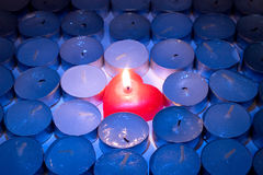 Burning and blown out candles. Burning red heart-shaped candle among rows of blown out candles Royalty Free Stock Photo
