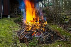 Burning of branches and garden waste, yellow and orange flames. royalty free stock photos