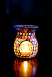 Burning Brightly. Candle and oil burner. The oil burner is made of glass in a mosaic pattern that has the most lovely lighting Royalty Free Stock Photos