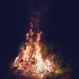 Burning brushwood on fire at night, seasonal cleaning of the countryside area, spurts of flame rising up in the air royalty free stock photography