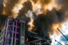 Burning building in thick toxic smoke. Big fire stock images