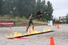 Burning Bunny Hop. A young man leaps the Pyromaniac fire obstacle. Rugged Maniac Competition, August 15, 2015, Vancouver, BC stock photos