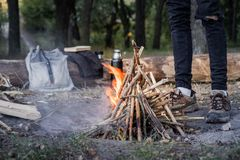 Burning campfire near a forest. Travelling into the wild concept. Camping place with vintage backpack, thermos and male feet in trekking shoes near a fireplace stock image