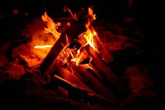Burning campfire outdoors. Close-up of burning firewood logs in campfire placed on sand outdoors at night stock photos