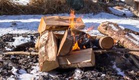 Burning campfire during winter picnic. Burning campfire with flames during winter picnic at day time stock photo
