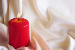 Burning candle. On a background of a drapery Stock Photo