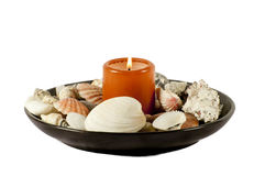Burning candle. With shells isolated on a white background Stock Photos