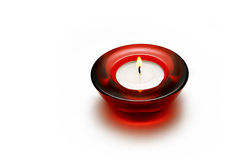 Burning candle. A burning candle in a round red glass candlestick on a white background Royalty Free Stock Photos
