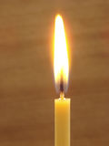 Burning candle. At the brown background Stock Photo